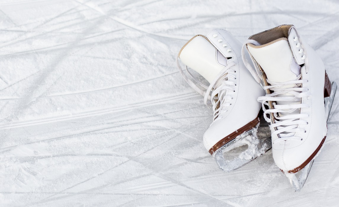 close up of white figure skates and copy space over ice background with marks from skating or hockey